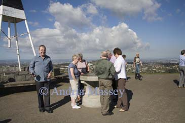 AUCKLAND NORTH ISLAND NEW ZEALAND May Group of tourists looking at the metal map information point on Mount Eden