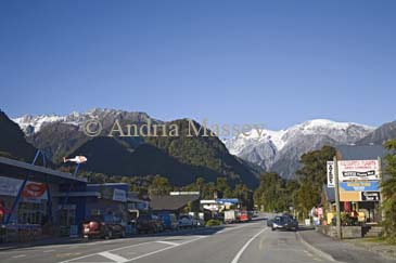FRANZ JOSEF WEST COAST SOUTH ISLAND NEW ZEALAND May Looking up the main street of this small village with the snow covered Southern Alps towering in the background