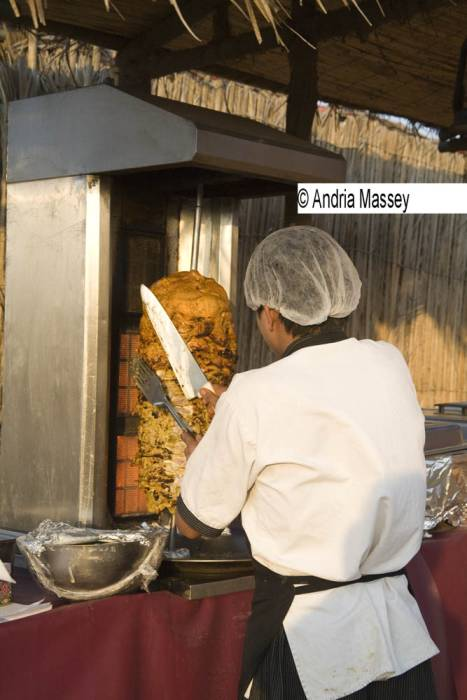 Dubai United Arab Emirates Young Bedouin male chef slicing a doner kebab on a vertical spit