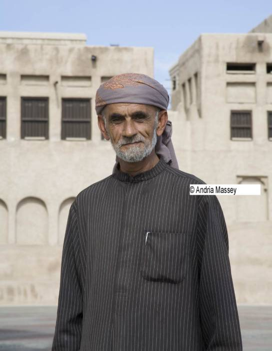 Dubai United Arab Emirates  Elderly Arab man wearing a dark pin striped Thobe and lilac and orange keffiyeh head dress