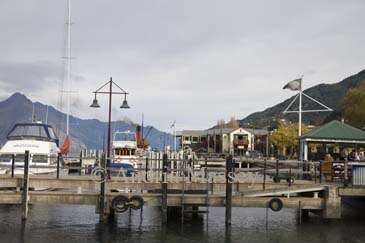 QUEENSTOWN SOUTHERN LAKES SOUTH ISLAND NEW ZEALAND May Moored motorboats and yachts at Steamer Quay on Lake Wakatipu of this charming small town