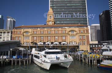 AUCKLAND NORTH ISLAND NEW ZEALAND May The rich red and tan colours of the sandstone and brick of the beautiful waterfront 1912 Ferry Building from Queens Wharf in Waitemata Harbour