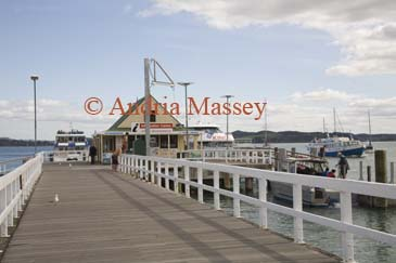 RUSSELL BAY OF ISLANDS NORTH ISLAND NEW ZEALAND May Looking along the wooden boardwalk of the ferry terminal wharf with excursion boats coming and going