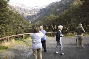 ARTHURS PASS CENTRAL SOUTH ISLAND NEW ZEALAND May Group of tourists photographing the snow covered Mount Rolleston from a roadside viewpoint