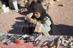 Sinai Desert Egypt North Africa February A young Bedouin girl sorting out trinkets laid out on a wall for sale to passing tourists