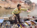 VARANASI UTTAR PRADESH INDIA November Hawker trying to sell  souvenirs to visitors travelling along the River Ganges viewing the historic Ghats - stepped embankments